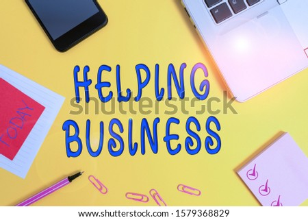 Text sign showing Helping Business. Conceptual photo improving some measure of an enterprise s is success Laptop smartphone notepad marker paper sheet note clips colored background.