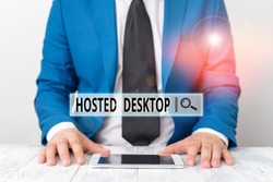 Text sign showing Hosted Desktop. Conceptual photo product set within the larger cloudcomputing sphere Businessman in blue suite with a tie holds lap top in hands.