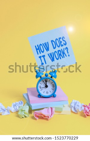 Text sign showing How Does It Work Question. Conceptual photo Asking on how stuff being build or operates Alarm clock sticky note paper balls stacked notepads colored background.