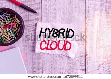 Text sign showing Hybrid Cloud. Conceptual photo computing environment that combines public and a private cloud Wrinkle paper and notebook plus stationary placed above wooden background. stock photo