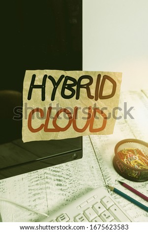 Text sign showing Hybrid Cloud. Conceptual photo computing environment that combines public and a private cloud Note paper taped to black computer screen near keyboard and stationary. stock photo