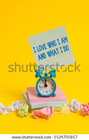 Text sign showing I Love Who I Am And What I Do. Conceptual photo High selfstem being comfortable with your job Alarm clock sticky note paper balls stacked notepads colored background.