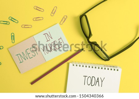 Text sign showing Invest In Yourself. Conceptual photo learn new things or materials thus making your lot better Square blank sticky notepads pencil clips eyeglasses yolk color background.