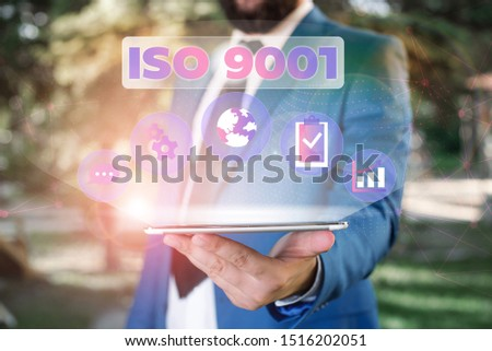 Text sign showing Iso 9001. Conceptual photo designed help organizations to ensure meet the needs of customers Male human wear formal work suit presenting presentation using smart device. #1516202051