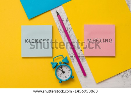Text sign showing Kickoff Meeting. Conceptual photo Special discussion on the legalities involved in the project Notepads marker pen colored paper sheets alarm clock wooden background.