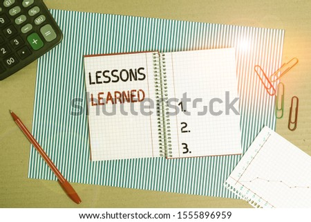 Text sign showing Lessons Learned. Conceptual photo the knowledge or understanding gained by experience Striped paperboard notebook cardboard office study supplies chart paper.