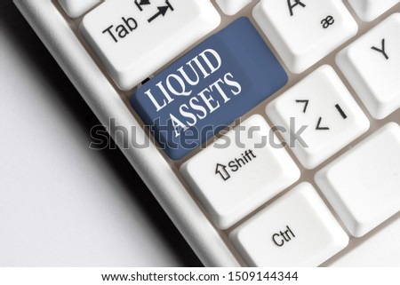 Text sign showing Liquid Assets. Conceptual photo Cash and Bank Balances Market Liquidity Deferred Stock White pc keyboard with empty note paper above white background key copy space. #1509144344