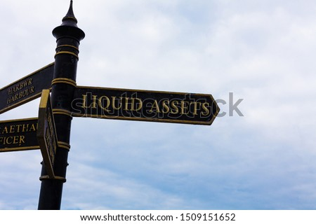 Text sign showing Liquid Assets. Conceptual photo Cash and Bank Balances Market Liquidity Deferred Stock Road sign on the crossroads with blue cloudy sky in the background. #1509151652
