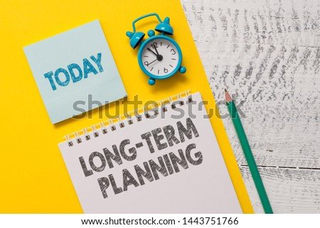 Text sign showing Long Term Planning. Conceptual photo Establish Expected Goals five or more years ahead Spiral notepad paper sheet marker alarm clock retro wooden background.