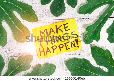 Text sign showing Make Things Happen. Conceptual photo you will have to make hard efforts in order to achieve it Leaves surrounding notepaper above a classic wooden table as the background.