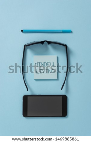Text sign showing Mindful Living. Conceptual photo Fully aware and engaged on something Conscious and Sensible Dark eyeglasses colored sticky note smartphone pen cool pastel background. #1469885861