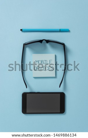 Text sign showing Mobile Devices. Conceptual photo A portable computing device like smartphone tablet computer Dark eyeglasses colored sticky note smartphone pen cool pastel background. #1469886134