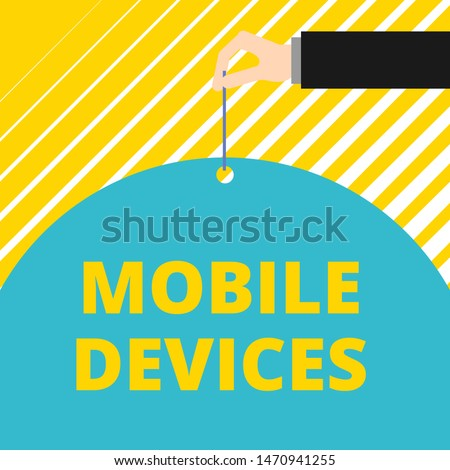 Text sign showing Mobile Devices. Conceptual photo A portable computing device like smartphone tablet computer Man hand hold big half round paper tie string with thumb and index finger.