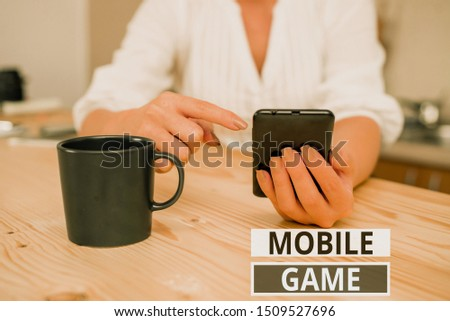 Text sign showing Mobile Game. Conceptual photo they are entertaining programs made to work on smart device woman using smartphone office supplies technological devices inside home. #1509527696