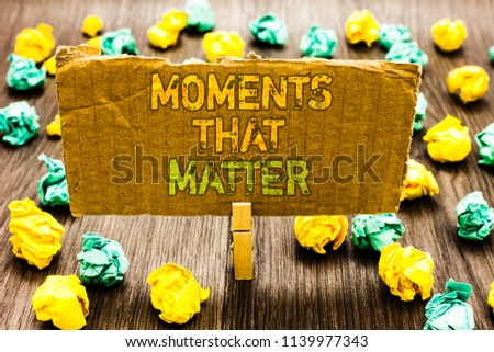 Text sign showing Moments That Matter. Conceptual photo Meaningful positive happy memorable important times Paperclip grip cardboard with texts many colorful lobs scattered on wooden desk. #1139977343