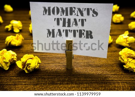 Text sign showing Moments That Matter. Conceptual photo Meaningful positive happy memorable important times Paperclip grip white page with grey text woody floor laid blurry yellow lob. #1139979959