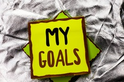 Text sign showing My Goals. Conceptual photo Goal Aim Strategy Determination Career Plan Objective Target Vision written on Stacked Sticky Note Paper on the Silver textured background.