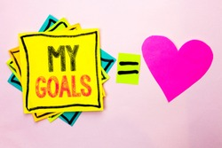 Text sign showing My Goals. Conceptual photo Goal Aim Strategy Determination Career Plan Objective Target Vision written on Stacked Sticky Note Papers on the plain background with Heart next to it.