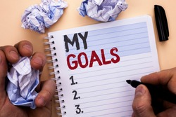 Text sign showing My Goals. Conceptual photo Goal Aim Strategy Determination Career Plan Objective Target Vision written by Man on Notebook Book holding Marker on Plain background
