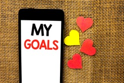 Text sign showing My Goals. Conceptual photo Goal Aim Strategy Determination Career Plan Objective Target Vision written on Cardboard Piece Holding By Sculpture on the jute background.
