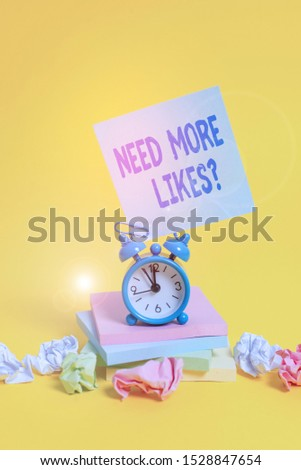 Text sign showing Need More Likes Question. Conceptual photo asking if he needs additional reaction on his post Alarm clock sticky note paper balls stacked notepads colored background.