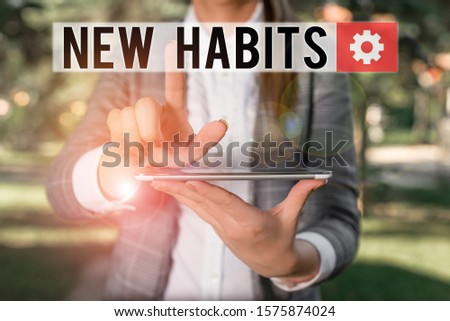 Text sign showing New Habits. Conceptual photo change the routine of behavior that is repeated regularly Outdoor scene with business woman holds lap top with touch screen.