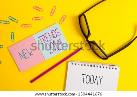 Text sign showing New Trends 2019. Conceptual photo general direction in which something is developing Square blank sticky notepads pencil clips eyeglasses yolk color background.