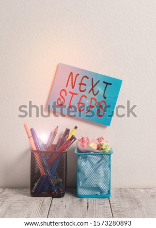 Text sign showing Next Steps. Conceptual photo numper of process going to be made after current one planning Blue Sticky Card on Wall Two Pencil Pots Pens Pencils Markers Waste Paper. #1573280893