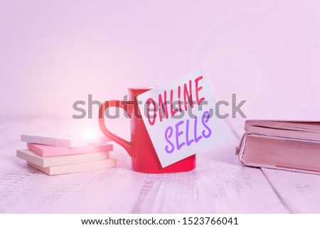 Text sign showing Online Sells. Conceptual photo sellers directly sell goods or services over the Internet Coffee cup blank sticky note stacked note pads books retro old wooden table.