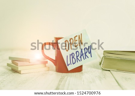 Text sign showing Open Library. Conceptual photo online access to analysisy public domain and outofprint books Coffee cup blank sticky note stacked note pads books retro old wooden table.
