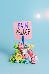 Text sign showing Pain Relief. Conceptual photo Drugs or other methods of reducing or getting rid of pain Reminder pile colored crumpled paper clothespin reminder blue background.