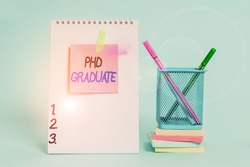 Text sign showing Phd Graduate. Conceptual photo highest university degree that is conferred after a course Spiral notebook sticky note banners stacked pads pens holder pastel back.