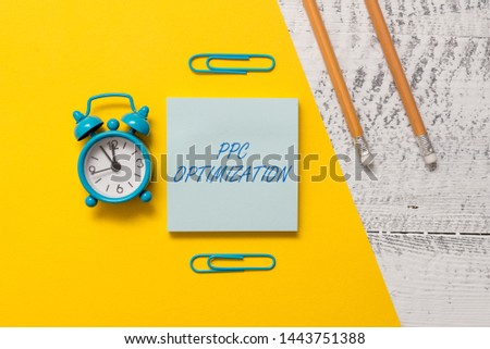 Text sign showing Ppc Optimization. Conceptual photo Enhancement of search engine platform for pay per click Notepad clips colored paper sheet markers alarm clock wooden background.