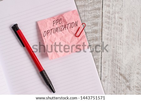 Text sign showing Ppc Optimization. Conceptual photo Enhancement of search engine platform for pay per click Wrinkle paper and notebook plus stationary placed above wooden background.