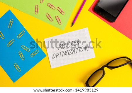 Text sign showing Process Optimization. Conceptual photo Improve Organizations Efficiency Maximize Throughput Paper sheets pencil clips smartphone eyeglasses notebook color background.