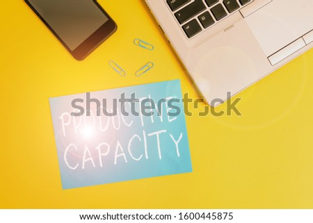 Text sign showing Productive Capacity. Conceptual photo the maximum possible output of a production plant Trendy open laptop smartphone small paper sheet clips colored background.