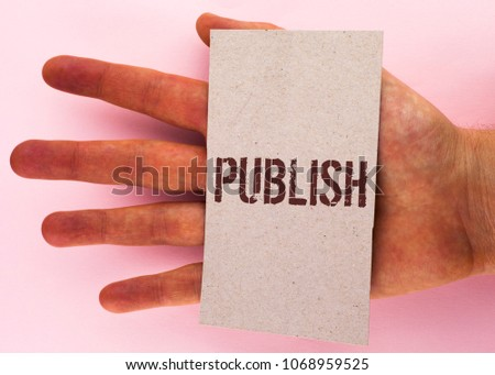 Text sign showing Publish. Conceptual photo Make information available to people Issue a written product written on Cardboard Piece placed on Hand on the plain background. #1068959525