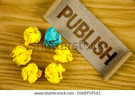 Text sign showing Publish. Conceptual photo Make information available to people Issue a written product written on Folded Cardboard Paper piece on wooden background Crumpled Paper Balls. #1068959561