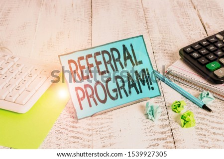 Text sign showing Referral Program. Conceptual photo internal recruitment method employed by organizations Notepaper stand on buffer wire in between computer keyboard and math sheets. #1539927305