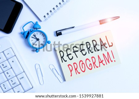 Text sign showing Referral Program. Conceptual photo internal recruitment method employed by organizations Flat lay above computer mobile phone clock pencil and copy space note paper. #1539927881