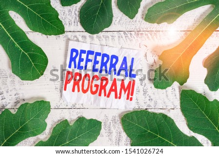Text sign showing Referral Program. Conceptual photo internal recruitment method employed by organizations Leaves surrounding notepaper above a classic wooden table as the background. #1541026724