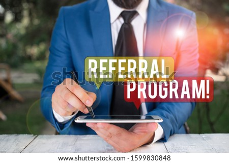 Text sign showing Referral Program. Conceptual photo internal recruitment method employed by organizations Businessman pointing with pen in empty copy space.