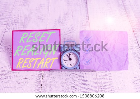 Text sign showing Reset Realign Restart. Conceptual photo Life audit will help you put things in perspectives Mini blue alarm clock standing above buffer wire between two notation paper. #1538806208