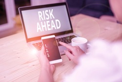 Text sign showing Risk Ahead. Conceptual photo A probability or threat of damage, injury, liability, loss woman laptop computer smartphone mug office supplies technological devices.