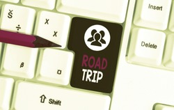 Text sign showing Road Trip. Conceptual photo Roaming around places with no definite or exact target location White pc keyboard with empty note paper above white background key copy space.