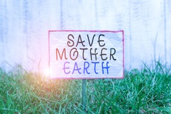 Text sign showing Save Mother Earth. Conceptual photo doing small actions prevent wasting water heat energy Crumpled paper attached to a stick and placed in the green grassy land.