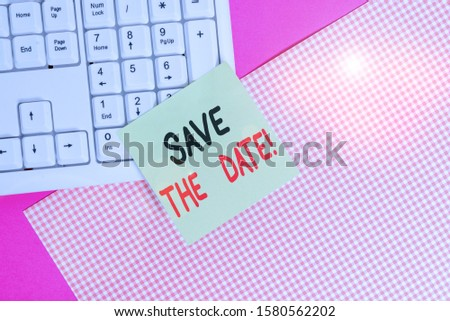 Text sign showing Save The Date. Conceptual photo Organizing events well make day special event organizers Note paper stick to computer keyboard near colored gift wrap sheet on table.