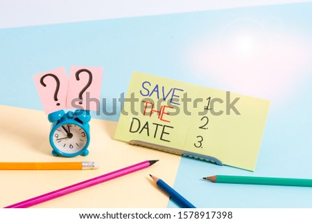 Text sign showing Save The Date. Conceptual photo Systematized events Scheduled activity Recorded Filed Mini size alarm clock beside stationary placed tilted on pastel backdrop.