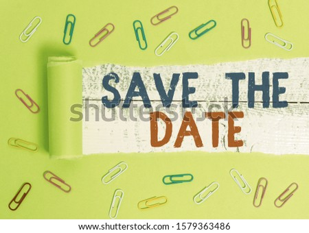 Text sign showing Save The Date. Conceptual photo Systematized events Scheduled activity Recorded Filed Paper clip and torn cardboard placed above a wooden classic table backdrop.