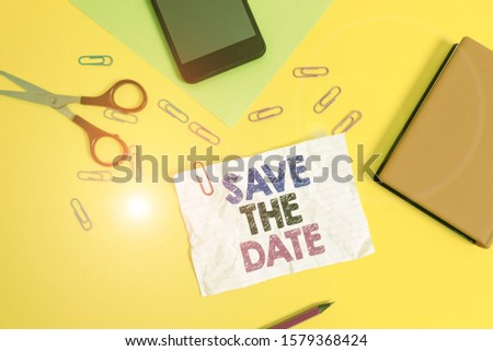 Text sign showing Save The Date. Conceptual photo Systematized events Scheduled activity Recorded Filed Paper sheets pencil clips smartphone scissors notebook colored background.